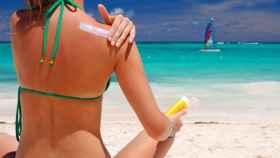 Una mujer se aplica protección solar.