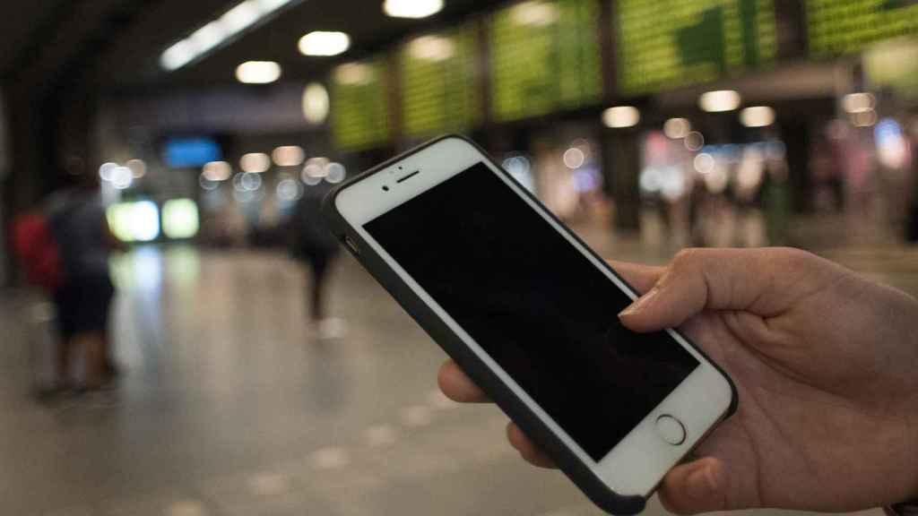 Una joven utiliza su móvil en un aeropuerto.