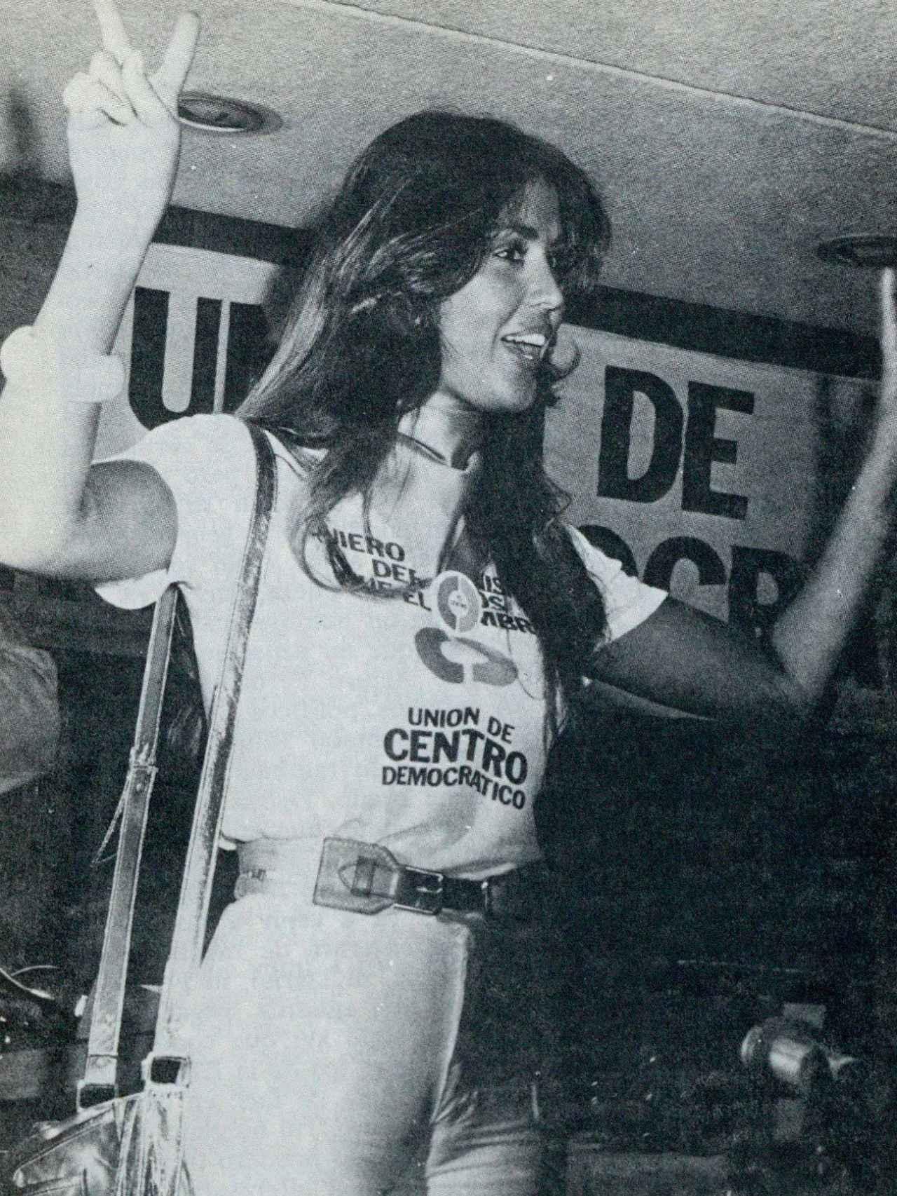 La Chica-Centro levanta las dos manos haciendo el signo de la victoria.