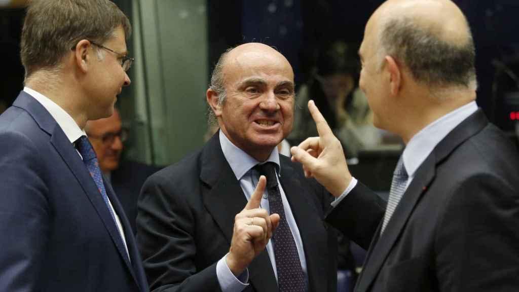 Guindos saluda a Moscovici y Dombrovskis durante la reunión del Eurogrupo
