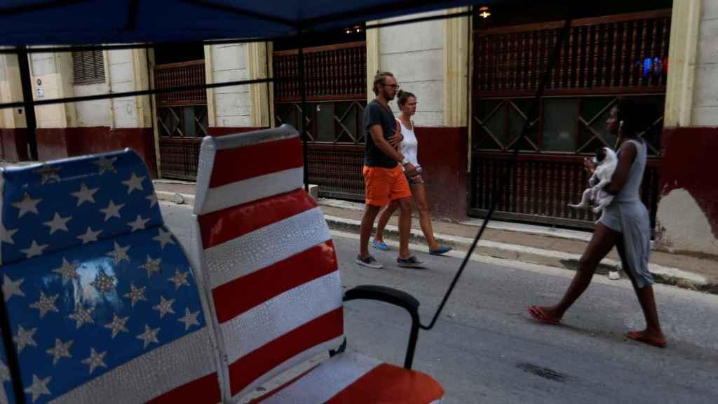 Dos turistas pasean por una calle de La Habana.