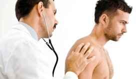 Un médico examina a un hombre con el estetoscopio.