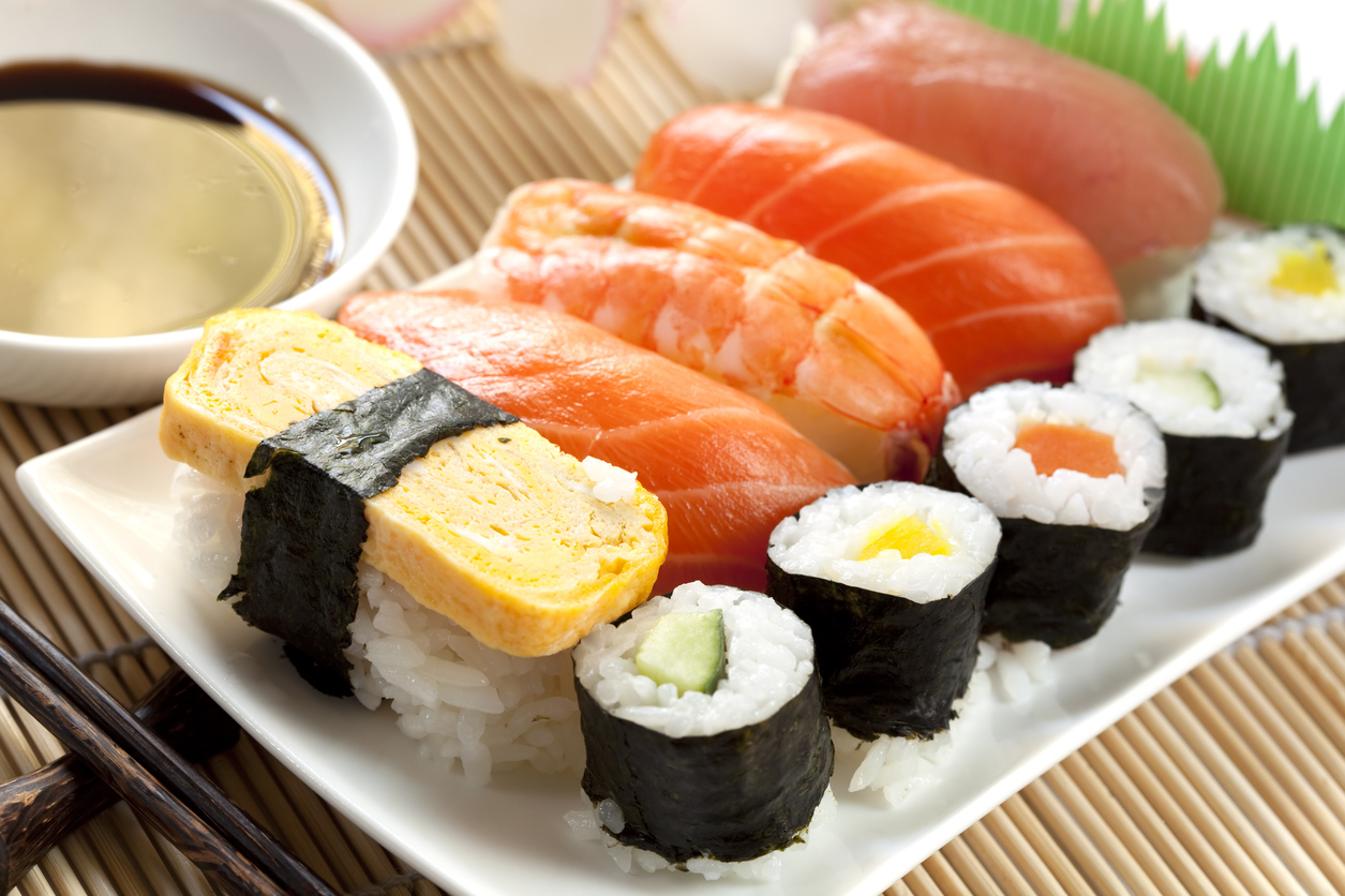 White plate of sushi with soy sauce and chopsticks
