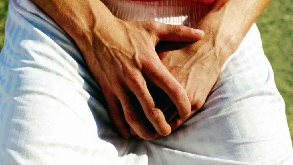 Un hombre sujeta sus testículos con las manos.