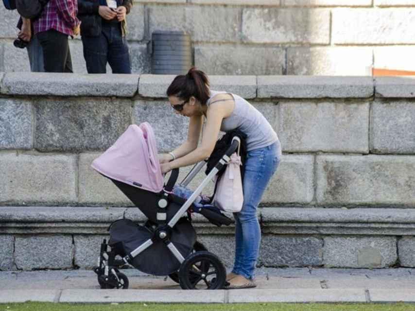 Una madre atiende a su bebé en la calle