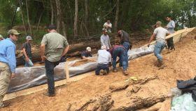 Un grupo de voluntarios, liderados por dos arqueólogos, protegen la canoa