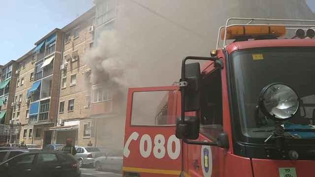 Los bomberos tratan de apagar el fuego de la vivienda de Málaga.