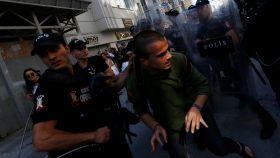 Un agente detiene a un joven que participaba en el desfile.