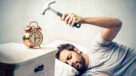 Un hombre golpea el despertador con un martillo.