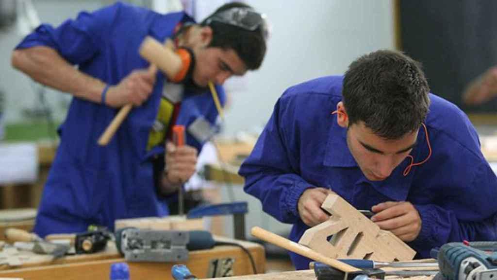 Dos jóvenes trabajando con una pieza madera.