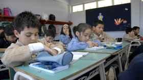 Un grupo de niños asiste a clase en un colegio.
