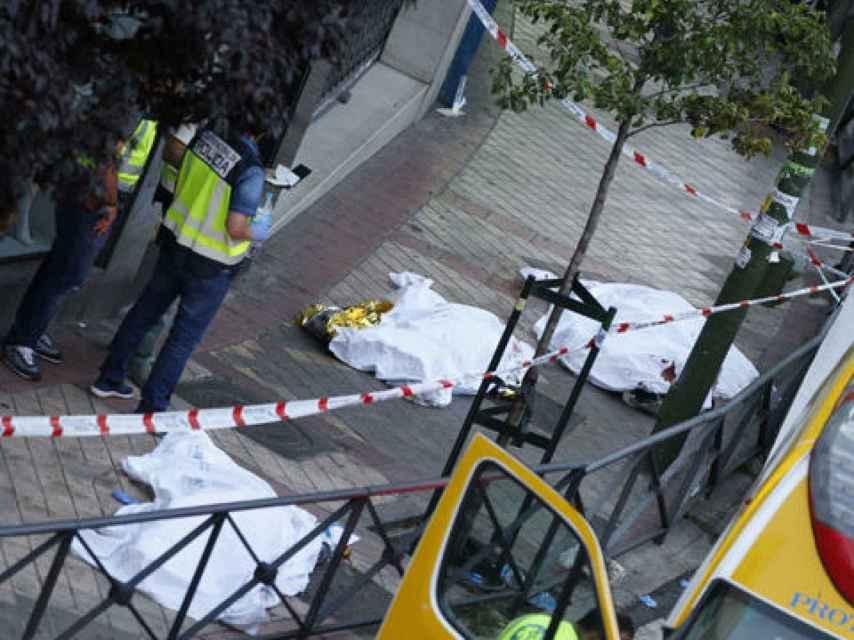 Cadáveres de los fallecidos, junto a los agentes de la Policía Científica, el día del crimen el año pasado.
