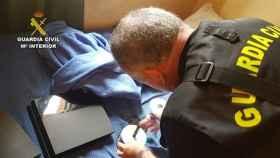 Un agente de la Guardia Civil, con los archivos incautados.