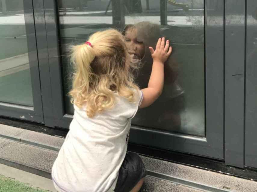 Malin, de dos años, mira por un cristal de su colegio a su hermano mayor.