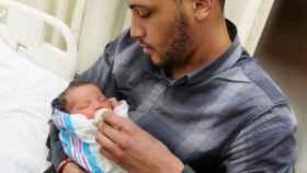 Un hombre da el biberón a un bebé que tiene cogido.