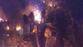 Los equipos de extinción trabajan por tierra combatiendo las llamas.