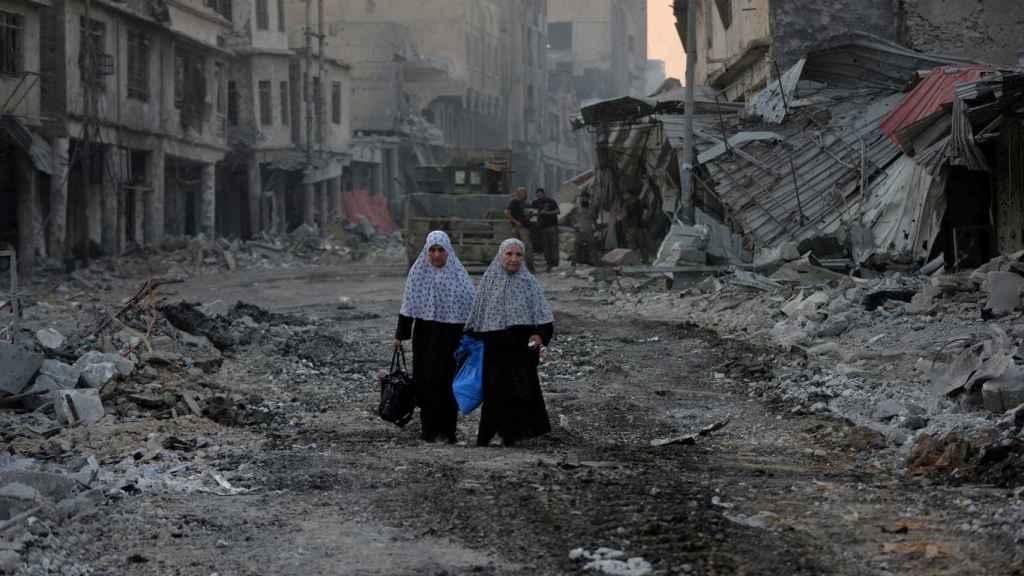 Dos mujeres desplazadas caminan entre los escombros de Mosul
