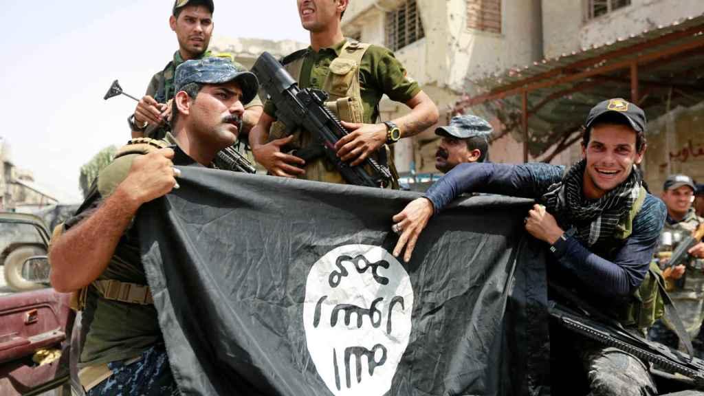 Soldados de Irak hacen el símbolo de la victoria con una bandera del ISIS en Mosul