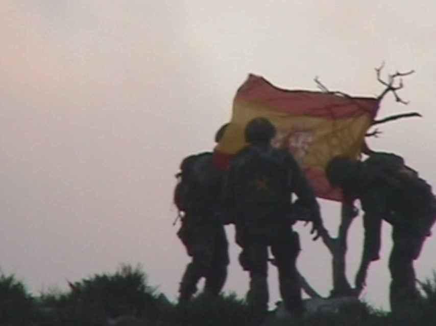 Los soldados de la misión plantan la bandera española en el islote.