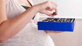 Una mujer embarazada sostiene una caja de bombones.