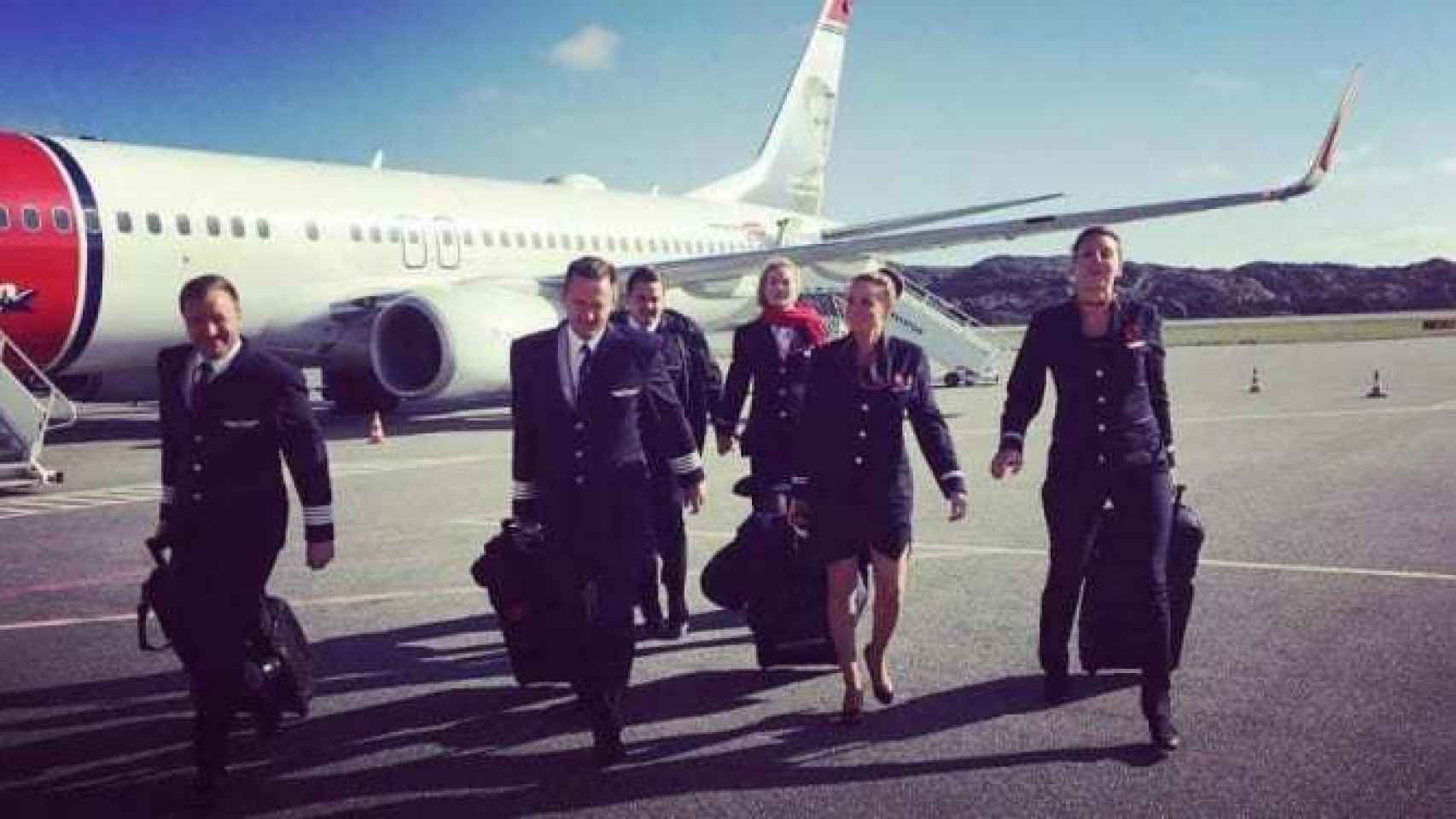 Un grupo de tripulantes de  Norwegian caminan por el aeropuerto.
