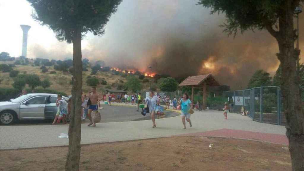 Las personas huyen del lugar con las llamas al fondo