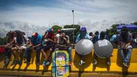 Varios escuderos descansan sentados en una mediana de la autopista Francisco Fajardo.