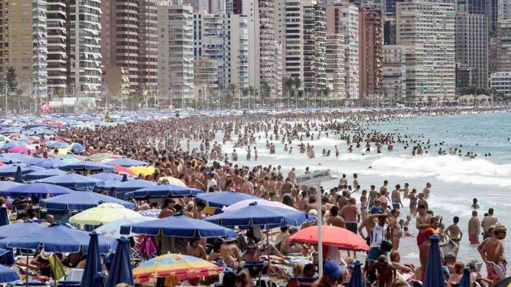 Una playa llena de bañistas.