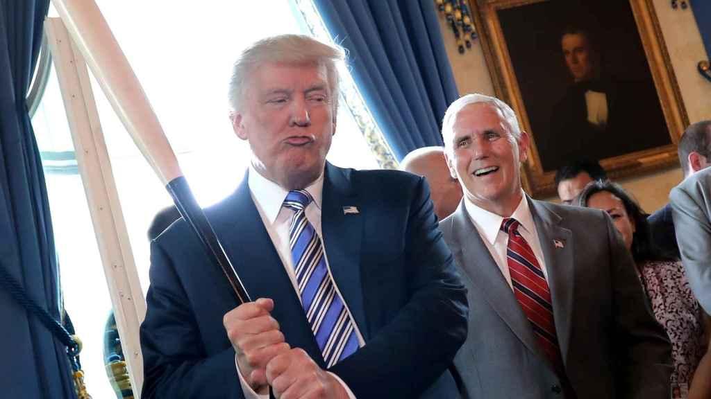 Trump sostiene un bate de béisbol ante la mirada de su vicepresidente, Mike Pence.
