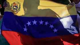 Un opositor levanta la bandera de Venezuela tras la consulta plebiscitaria.