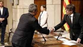 Joaquim Forn toma posesión como nuevo 'conseller' de Interior junto al presidente Carles Puigdemont.