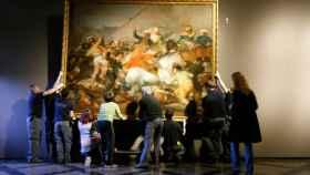 Empleados del Prado cuelgan la Carga de los mamelucos, tras ser restaurado.