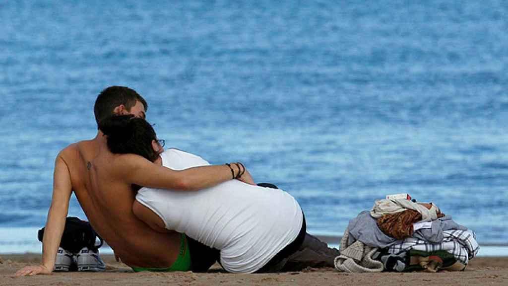 Una pareja disfruta de un día de playa entre arrumacos.