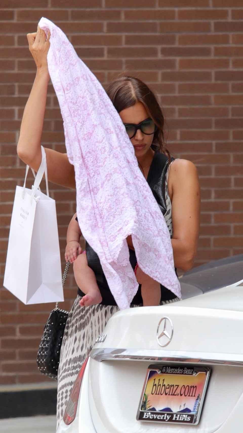 La maniquí tratando de ocultar el rostro de su hija.