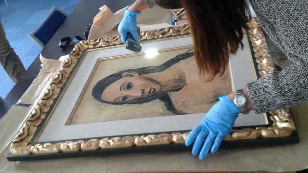 Restauradora del Reina Sofía revisando la obra a la llegada del museo.