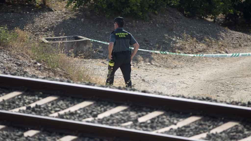 Un guardia civil inspecciona la zona acotada de la vía férrea donde ha sido encontrado el cuerpo de la niña