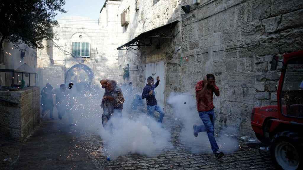 Un grupo de palestinos escapa de las gases lacrimógenas de la policía israelí