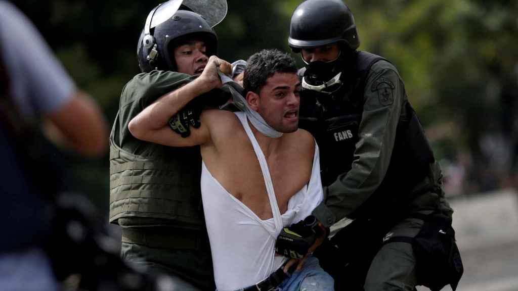 La policía venezolana detiene a un manifestante en una manifestación en Caracas