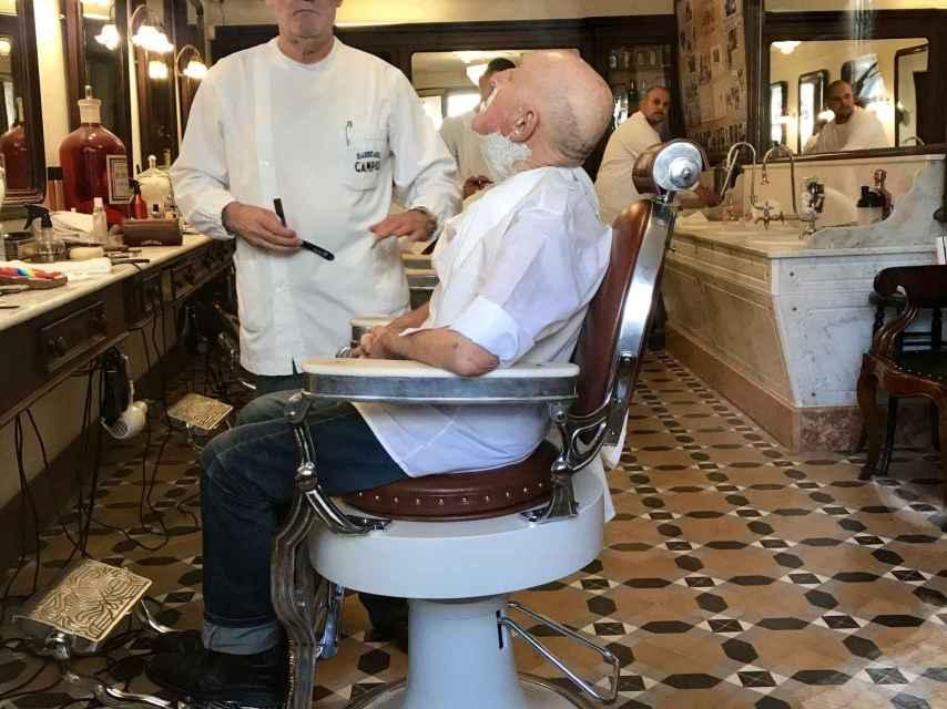 El peluquero posa mientras realiza su trabajo.