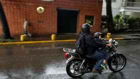 Un motorista pasa cerca de la embajada española en Caracas