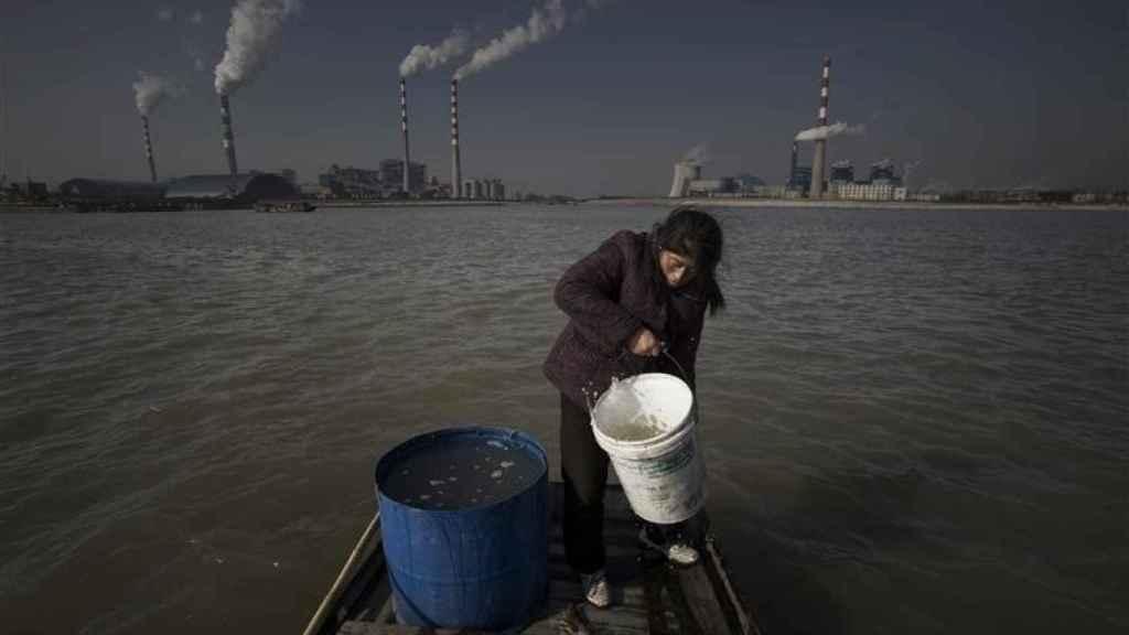 Una mujer recoge agua contaminada para consumo doméstico.