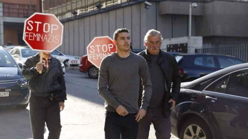 Lucas Hernández llegando a los juzgados escoltado por hombres con pancartas de Stop feminazis.