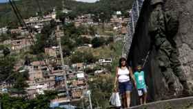 Un militar patrulla frente a una mujer y su hijo durante la operación en Río de Janeiro.
