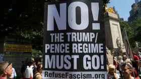 Uno manifestante expone un cartel contra lo que llama el régimen de Trump.