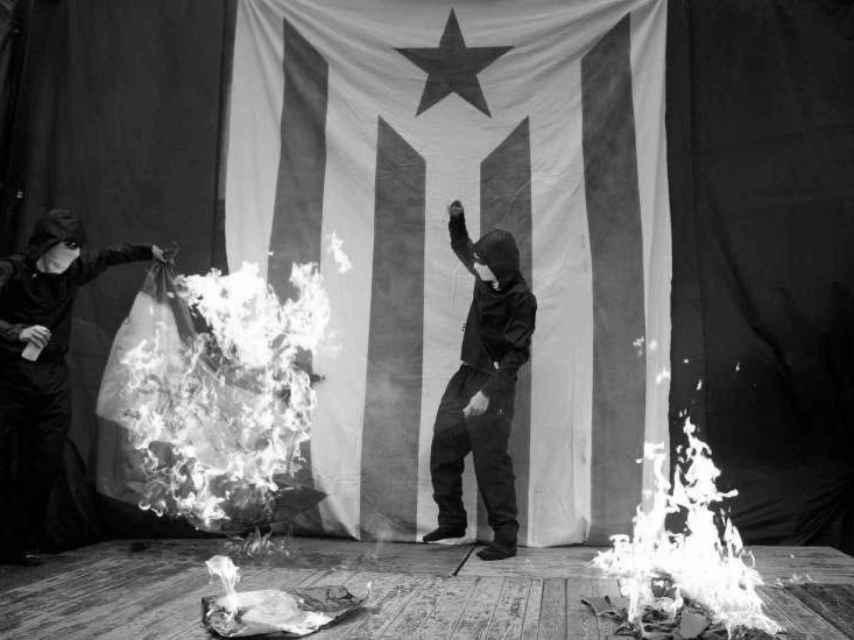 Encapuchados queman una bandera de España tras la Diada de 2011.