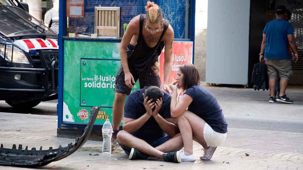 Varios jóvenes permanecen junto a los restos de un vehículo en el lugar del atentado.