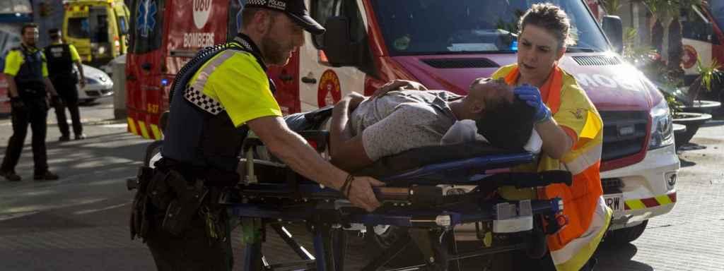 Los bomberos trasladan a uno de los heridos a la ambulancia