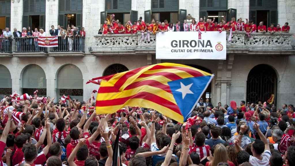 La afición del Girona FC celebra el ascenso del equipo frente al Ayuntamiento de la localidad.