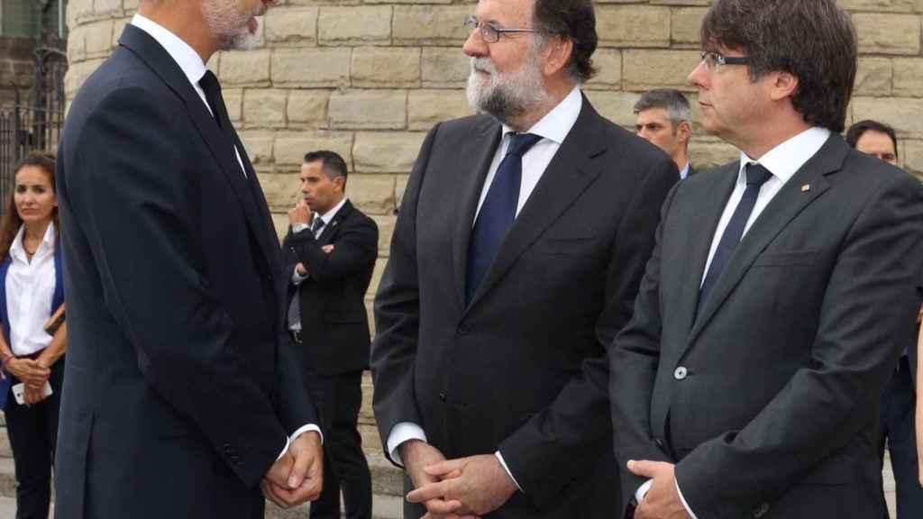 El rey Felipe VI junto a Rajoy y Puigdemont.
