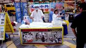 Miembros de Fulang Gong simulan una extracción de órganos como protesta.